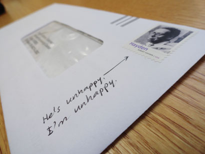 Writing on an envelope - showing how I am unhappy - pointing to a postage stamp of an unhappy person