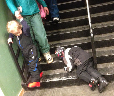 Skier kid asleep on a staircase