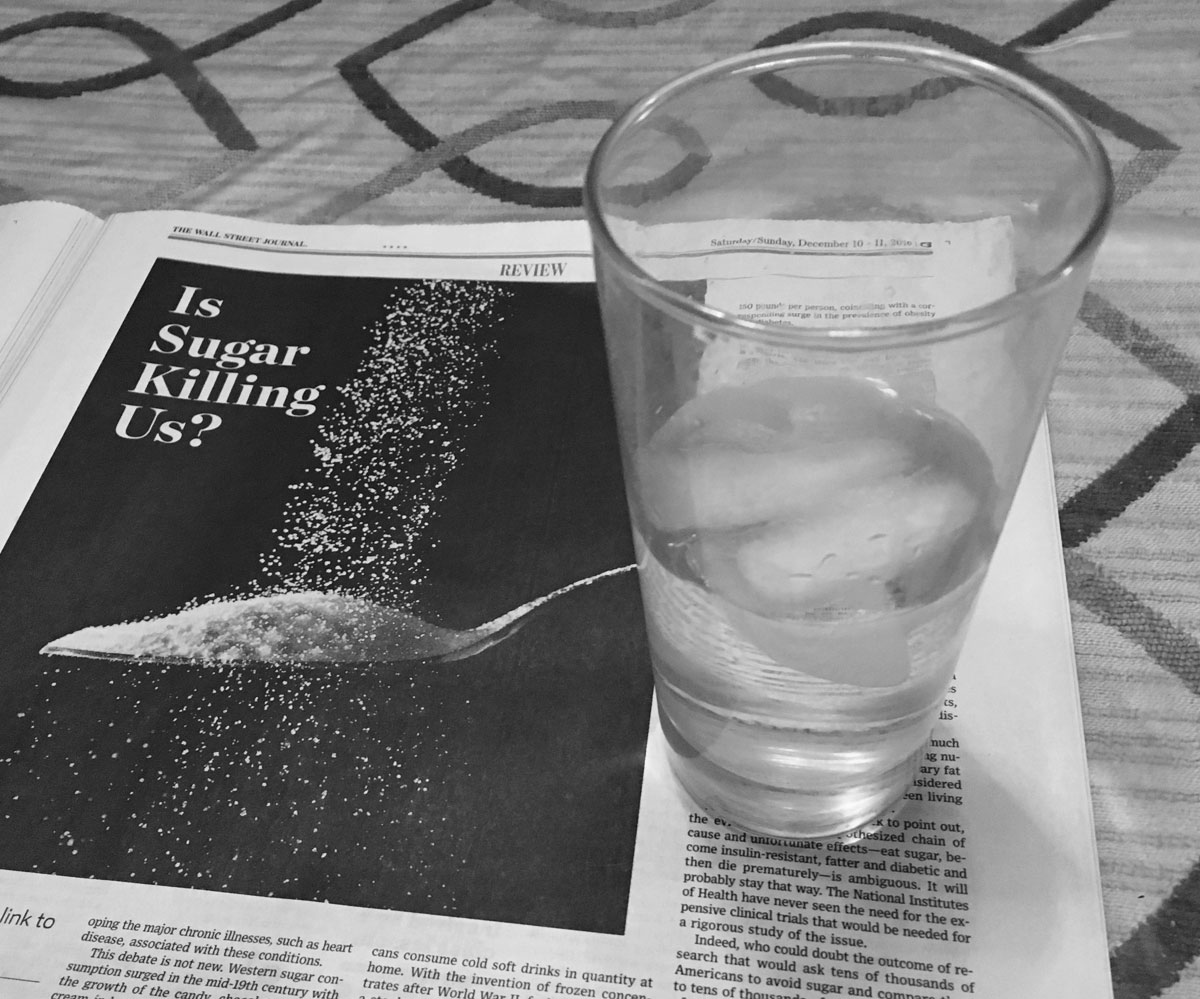 article about the evils of sugar with a cup of water